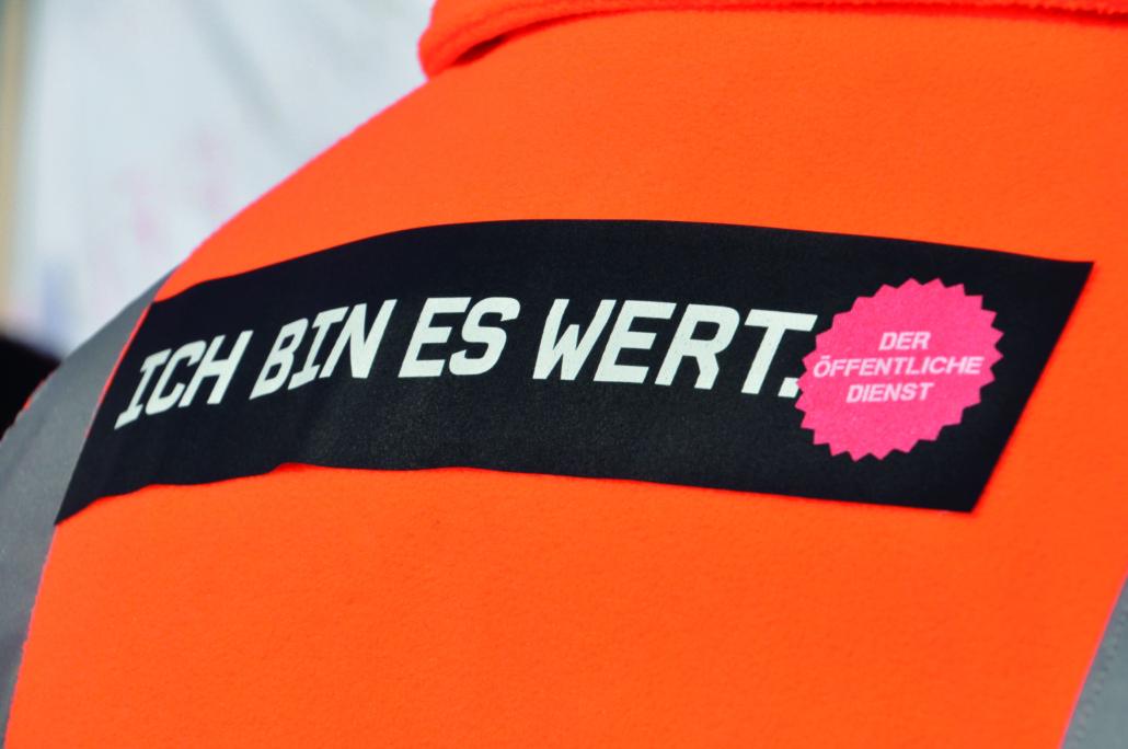 orange Weste mit der Aufschrift: Ich bin es wert.